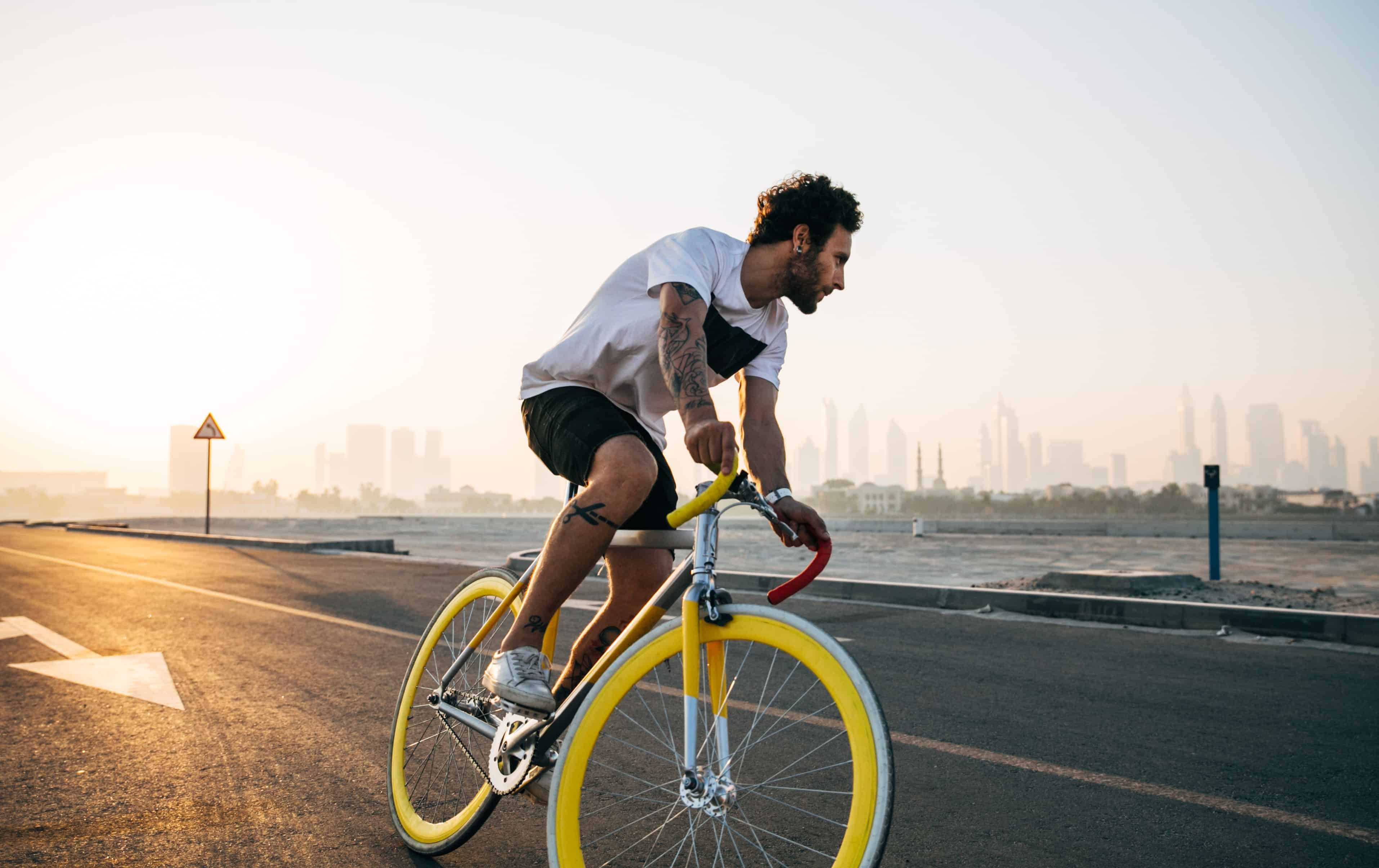 man riding yellow bicycle